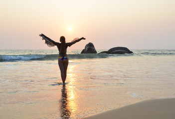 Young woman meditating on Agonda beach. South Goa, India
