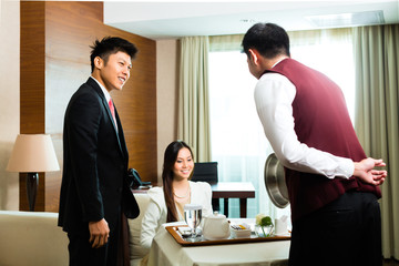 Asian Chinese room waiter serving food in hotel suite