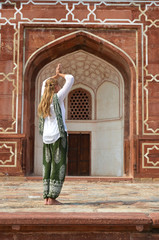 Young woman meditating in the yard of Humayun's Tomb. Delhi, Ind