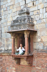Young woman meditating on the balcony of Bara Gumbad temple. Del