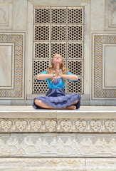 Young woman meditating at the wall of Taj Mahal. Agra, India