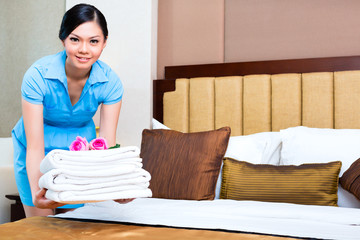 Chambermaid cleaning in Asian hotel room