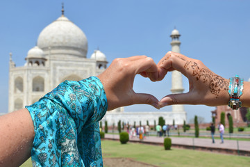 Heart-shaped hands against Taj Mahal. Agra, India