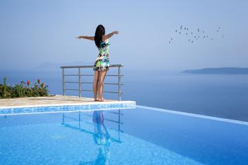 Frau in Abendkleid steht am Pool und breitet die Arme aus