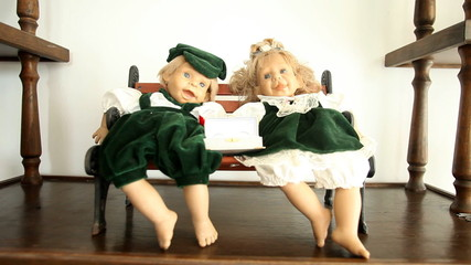 Two cute dressed dolls seated on small chair