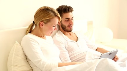 Young couple with a Tablet PC in Bed