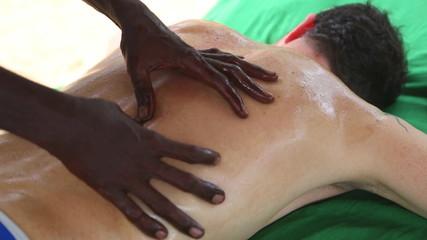 Sri Lankan man giving full back oil massage to Caucasian man
