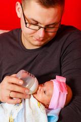 father feeding newborn baby girl with milk bottle