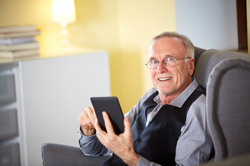 Senior man at home reading on a e-book