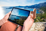 Holding digital tablet on the mountain