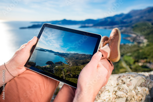 Holding digital tablet on the mountain - 81261062