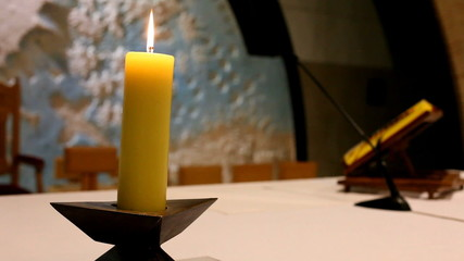 Burning candle on altar in church