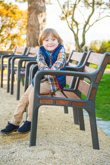 Funny little boy resting on a bench in the park