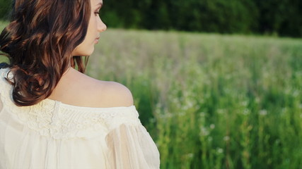 A young girl with bare shoulders in the midst of green fields