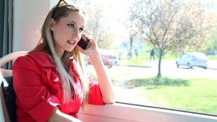 Beautiful woman sitting in tram, talking on phone