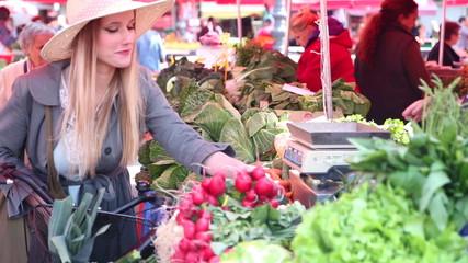 Pretty girl picking radish at the market