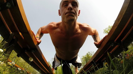 Close up of sports man doing push ups on bench