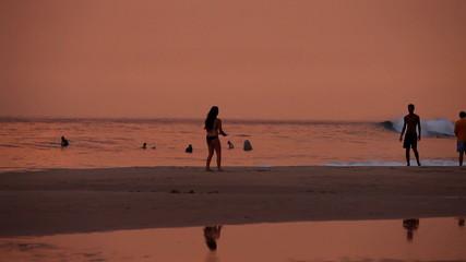 HIKKADUWA, SRI LANKA - FEBRUARY 2014: View of Hikkaduwa beach at sunset, while waves are splashing and people are playing with frisbee. Hikkaduwa is famous for its beaches.