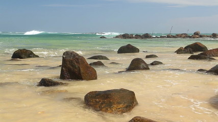 Big rocks on beautiful sandy beach in Sri Lanka