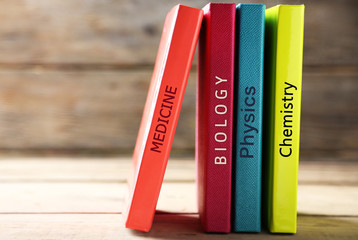 Colorful books on table on wooden background