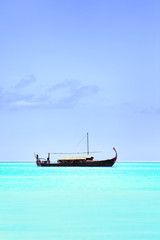 View of beautiful blue ocean water with boat in Baros Maldives