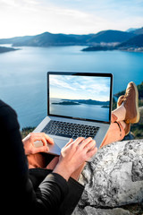 Man with laptop on the top of mountain
