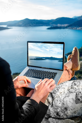 Foto op Canvas Alpinisme Man with laptop on the top of mountain