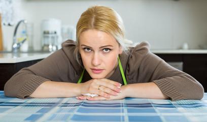 Sad woman sitting at kitchen