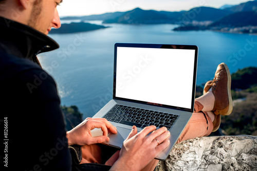 Leinwanddruck Bild Man with laptop on the top of mountain