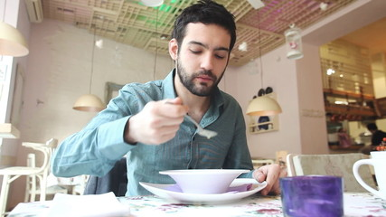Handsome young man eating in soup a restaurant
