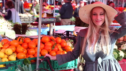 Blonde girl with bike is walking at the market, smiling