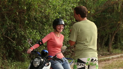 girl in motor helmet sits on scooter and laughs and guy gesticul