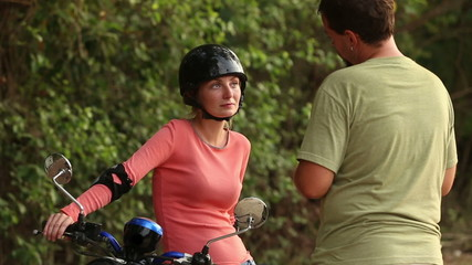 girl in motor helmet sits on scooter and listen to instructor
