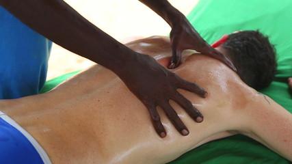 Sri Lankan man giving shoulder oil massage to Caucasian man