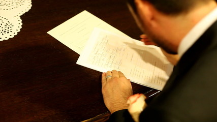 Groom signing wedding document