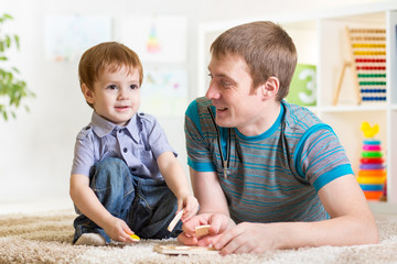 Child boy and father play with puzzle toy