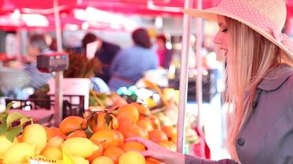 Blonde girl at the market picking oranges