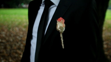 Groom wearing a rose on his tux waiting in garden