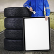 Mechanic with placard and tires