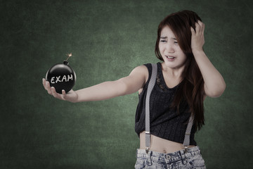Panic student holding a bomb with exam text