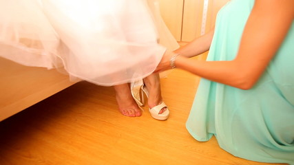 Woman helping bride to put wedding shoes on