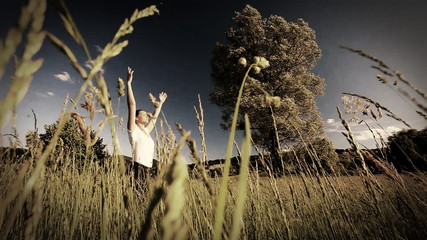 Woman doing yoga in the middle of a field of high grass - sepia style grading