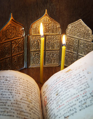 Orthodox Christian still life with open ancient book and candles