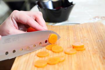 Chefs hands chopping carrot