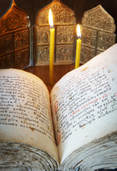 Orthodox Christian still life with open book and burning candles