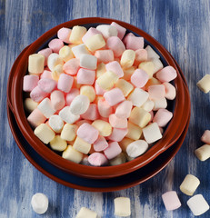 Colorful small marshmallows on a blue wooden background.