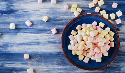 Colorful small marshmallows on  blue wooden background.