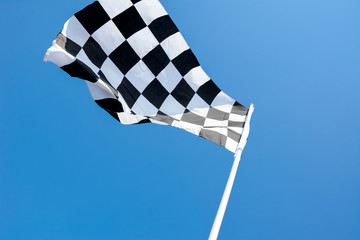 Checkered flag flying on blue sky background