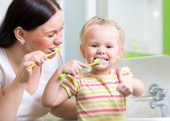 mother teaching child teeth brushing