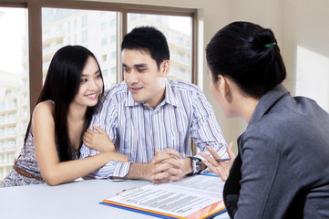 Young couple discussing with a financial agent